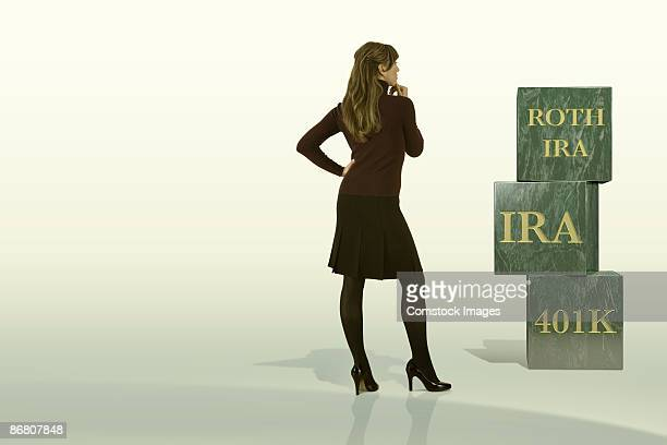Businesswoman looking at blocks for Roth IRA, IRA, and 401k