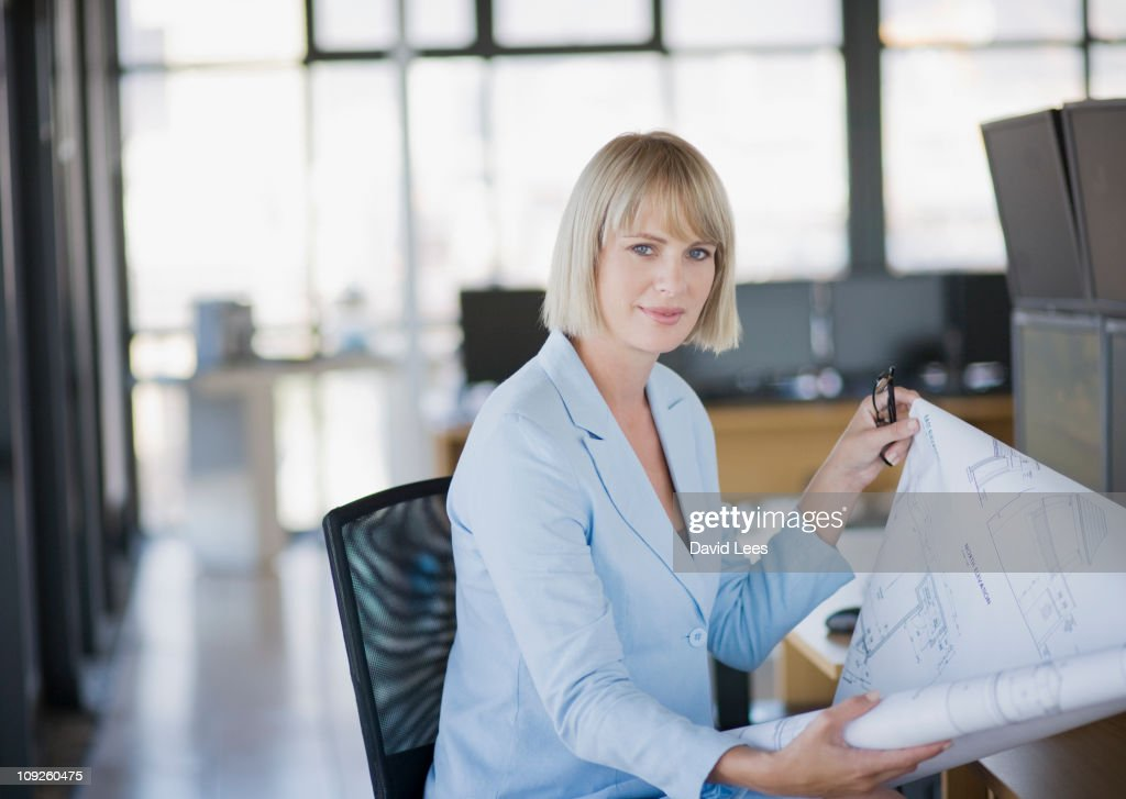 Businesswoman looking at blueprints : Stock Photo