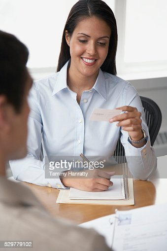 Businesswoman looking at business card : Stockfoto