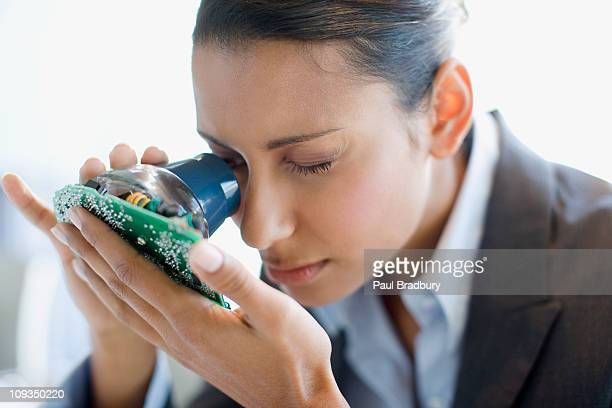 Businesswoman looking at circuit board