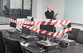 Businesswoman looking at computers covered in tape