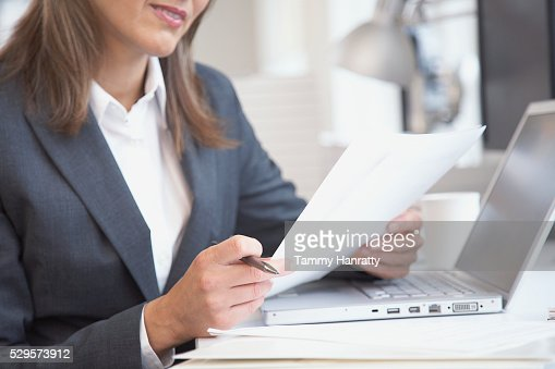 Businesswoman looking at document : Stock-Foto