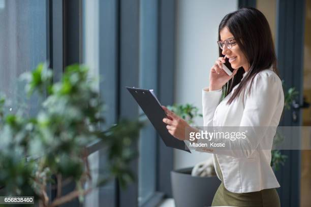 Businesswoman looking at documents and talking on phone