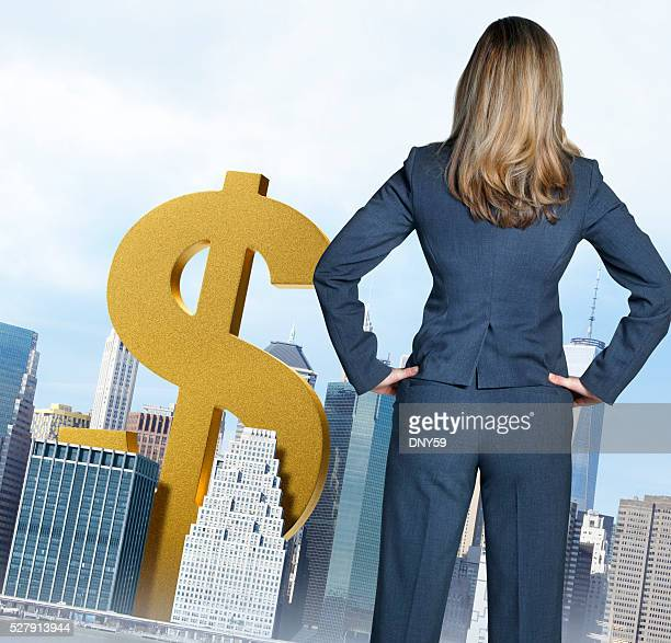 Businesswoman Looking At Dollar Sign Standing Among Skyscrapers