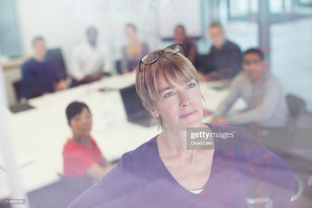 Businesswoman looking at glass wall in meeting : Stock Photo
