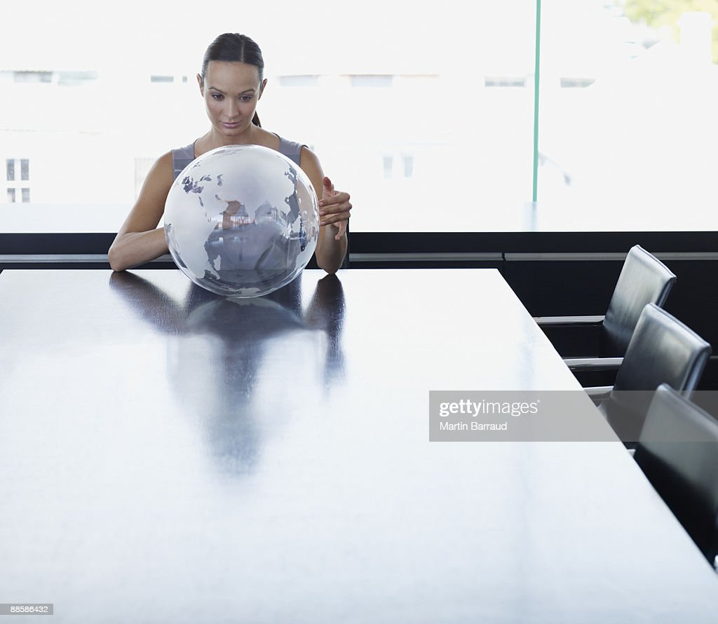 Businesswoman looking at globe in conference room : Stock Photo