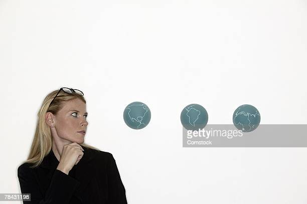 Businesswoman looking at globes