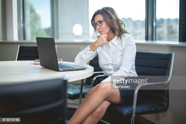 CEO businesswoman looking at laptop