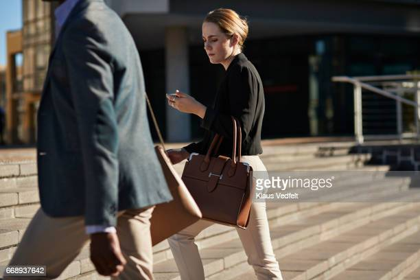 Businesswoman looking at phone, while walking on staircase