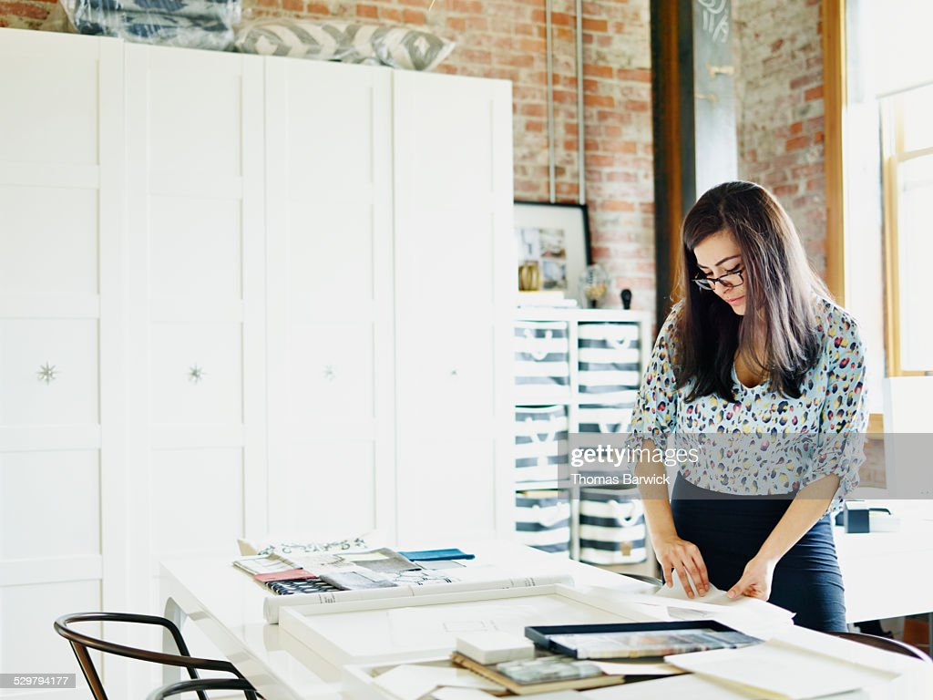 Businesswoman looking at plans in design firm