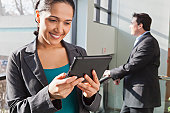 Businesswoman looking at tablet with businessman behind her
