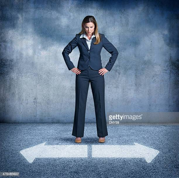 Businesswoman looking at two arrows pointing in opposite directions