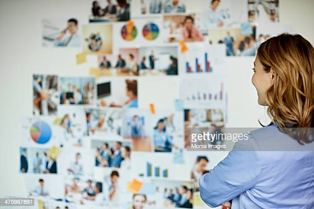 Businesswoman looking at wall with photos