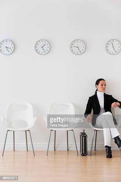 Businesswoman looking at wrist watch in waiting room
