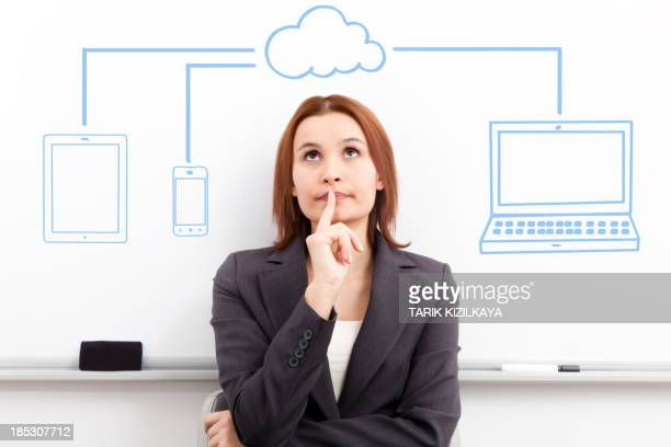 Businesswoman looking cloud computing diagram.
