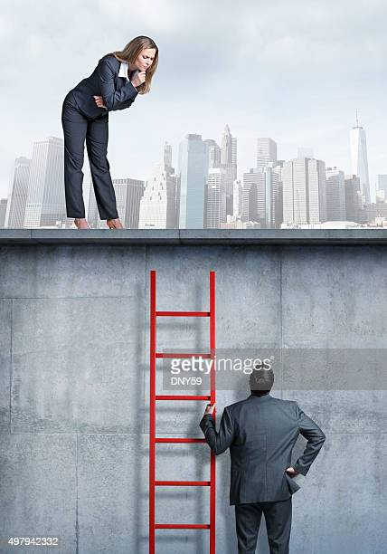 Businesswoman Looking Down At Businessman Holding A Ladder