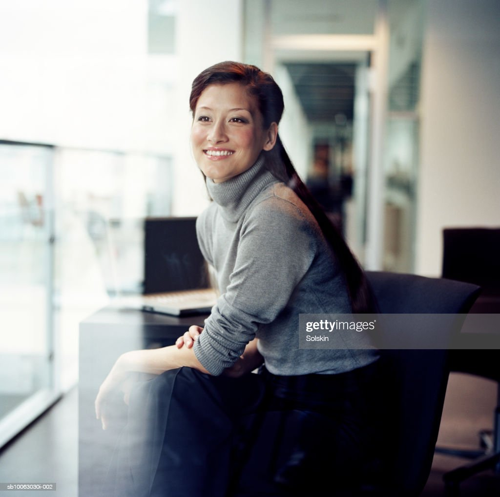 Businesswoman looking out of office window, smiling : Stock Photo