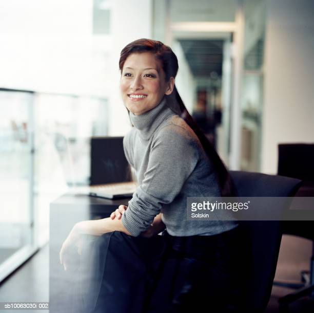 Businesswoman looking out of office window, smiling