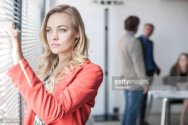 Businesswoman looking out office window with people in background