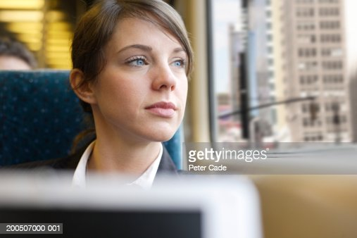 Businesswoman looking out window on train, close-up : Stock Photo
