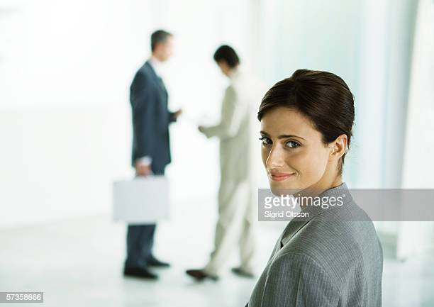 Businesswoman looking over shoulder in office lobby