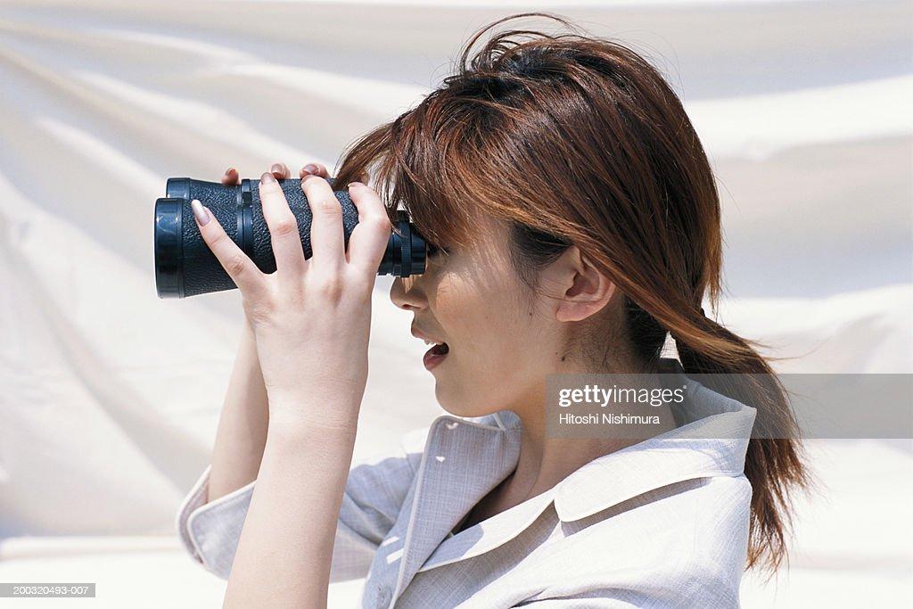 Businesswoman looking through binoculars, side view, close-up : Stock Photo