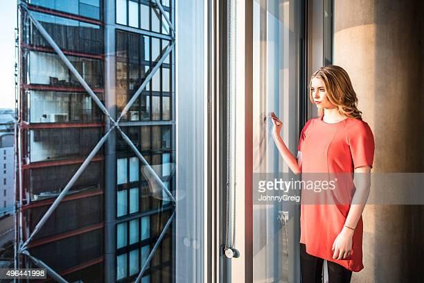 Femme d'affaires regardant par la fenêtre de bureau moderne