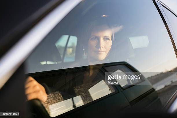 Businesswoman looking through window while driving car