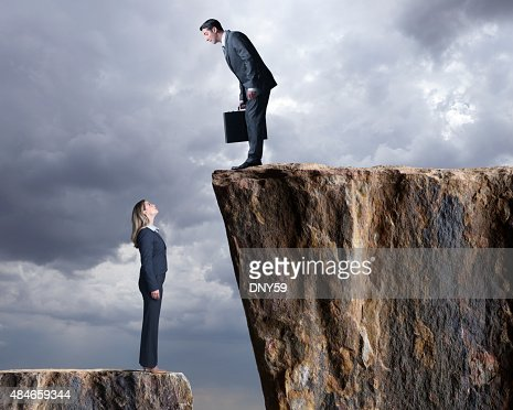 Businesswoman Looking Up At A Businessman Standing On Higher Level