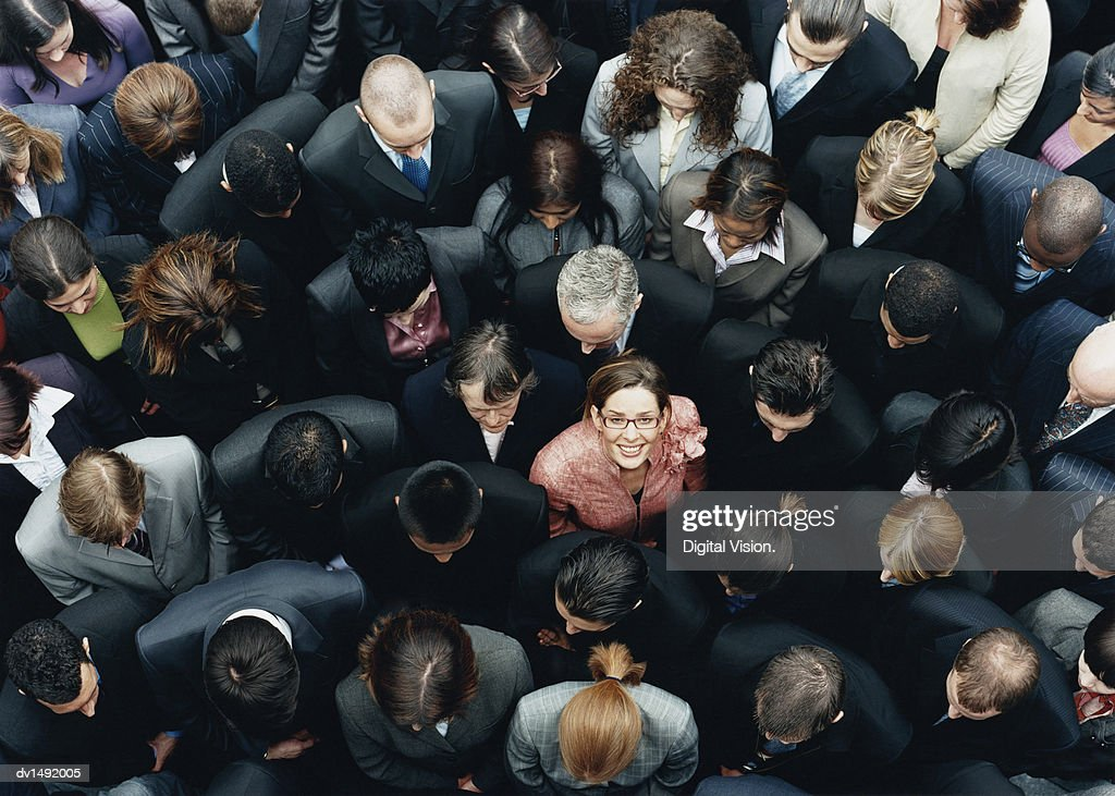 Businesswoman Looking up at Camera and Standing Outdoors Surrounded by a Large Group of Business People : Stock Photo