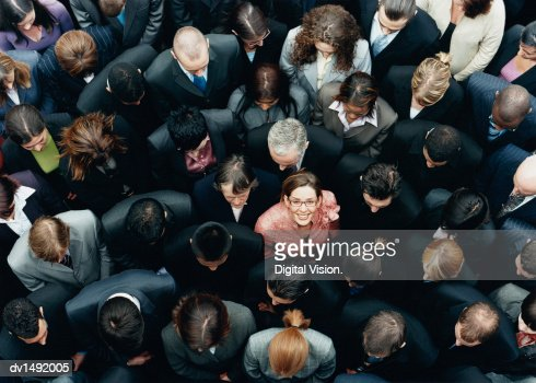 Businesswoman Looking up at Camera and Standing Outdoors Surrounded by a Large Group of Business People : Foto de stock