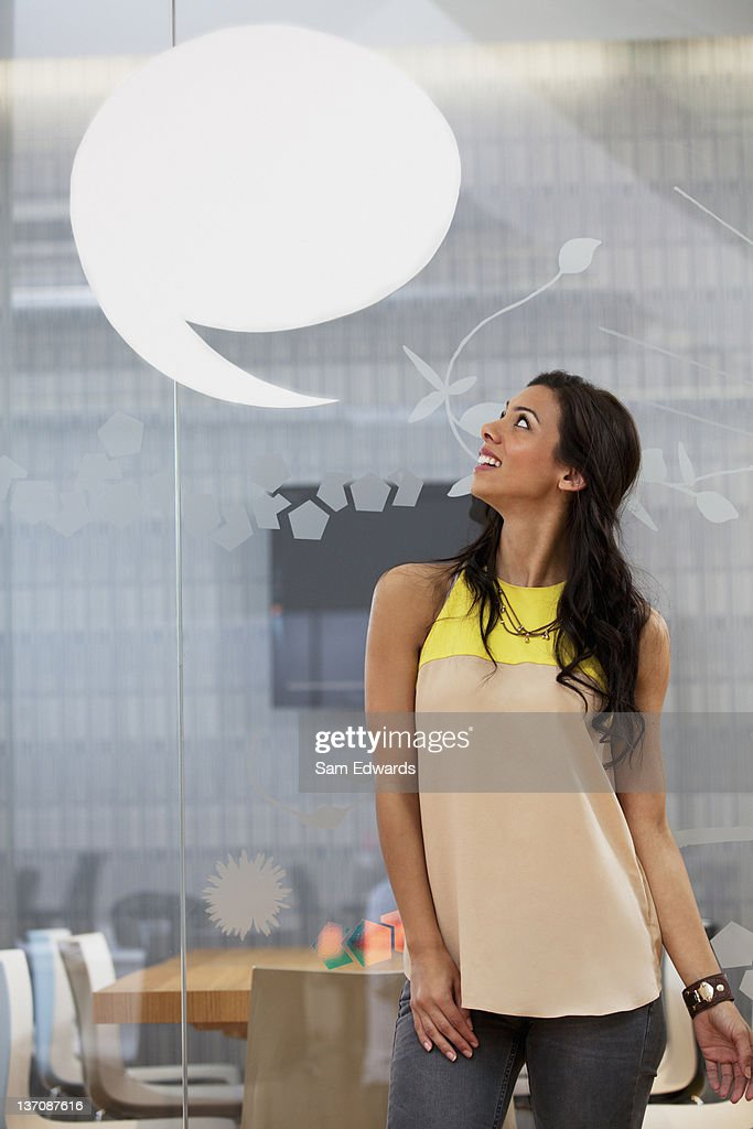 Businesswoman looking up at speech bubble overhead : Stock Photo