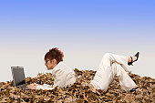 Businesswoman lying on dry leaves and working on a laptop