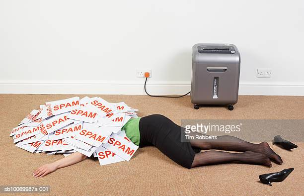 Businesswoman lying on floor with pile of spam envelopes, low section