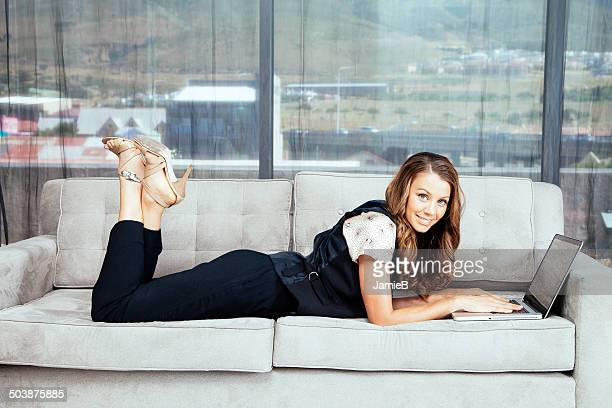 Businesswoman lying on sofa using laptop