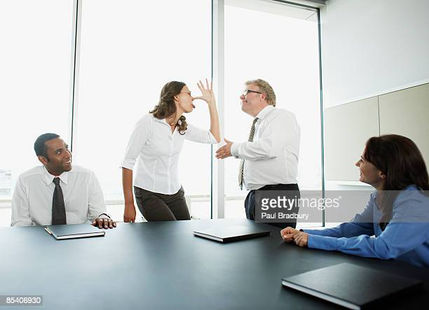Businesswoman making face at boss in conference room
