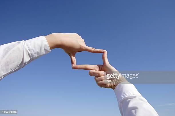 Businesswoman making finger frame against blue sky