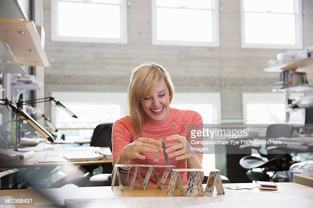 Businesswoman making house of cards in office