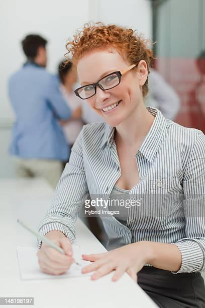 Femme d'affaires faisant des notes dans une réunion