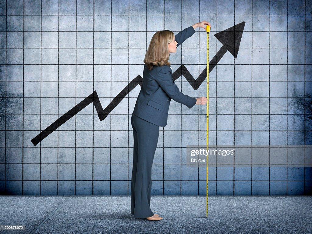 Geschäftsfrau misst Wachstum mit Maßband : Stock-Foto