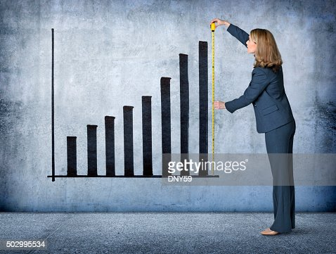 Businesswoman Measures Growth With Tape Measure