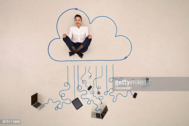 Businesswoman meditating in a cloud connected to mobile devices