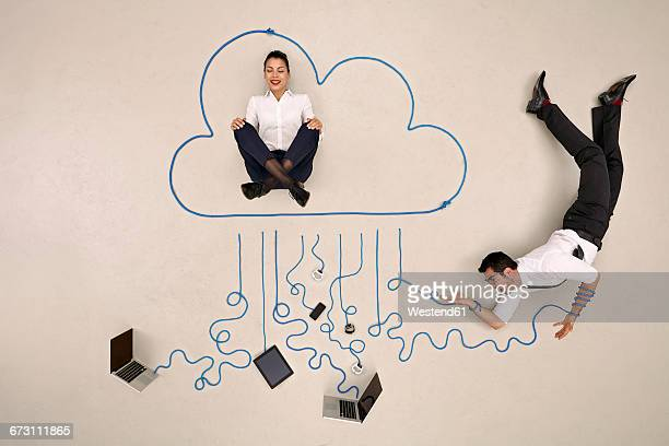 Businesswoman meditating in cloud, businessman tangled up in mobile devices