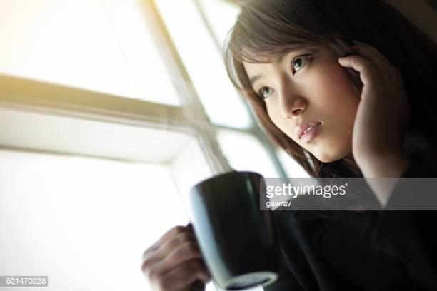 Businesswoman near glass window with coffee mug in her leisure.