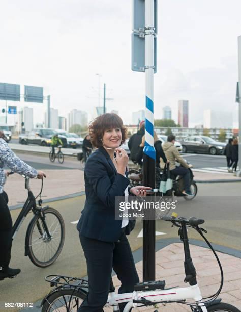businesswoman on bike , having a phone call on crossroads