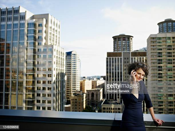 Businesswoman on cell phone cityscape behind
