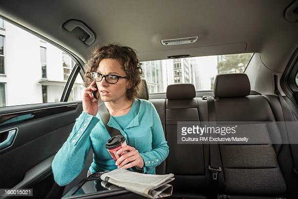 Businesswoman on cell phone in backseat