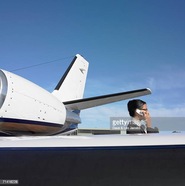 Businesswoman on cell phone next to airplane