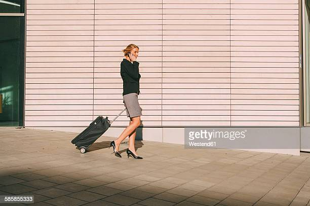 Businesswoman on cell phone walking with suitcase