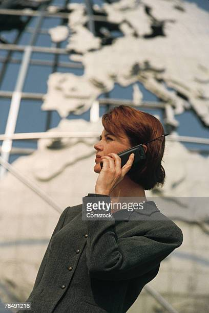 Businesswoman on cell phone with globe in background